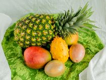 Ананас, манго, маракуйя и дыня kiwano на зеленой ткани стоковое изображение rf