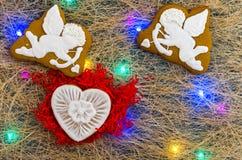 2 ангела ` s купидона и белого сердце gingerbread Пестротканая гирлянда Плоское положение Стоковая Фотография