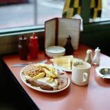 Английский завтрак с сосиской, яйцом, ветчиной, фасолями и зажаренными тостами, который служат в кафе стоковая фотография rf