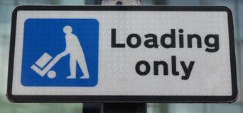 Английский знак улицы показывая паркуя ограничения, нагружая только стоковая фотография