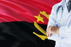 Ангольское положение доктора со стетоскопом на предпосылке флага Анголы Национальная концепция системы здравоохранения, медицинск стоковая фотография