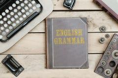 Английская грамматика на старой обложке книги на столе офиса с годом сбора винограда оно Стоковые Изображения