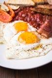 Английский завтрак & x28; яичницы, фасоли, зажарили в духовке бекон, сосиски и vegetables& x29; Стоковая Фотография RF