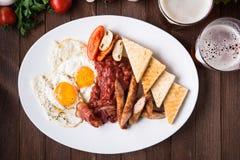 Английский завтрак & x28; яичницы, фасоли, зажарили в духовке бекон, сосиски и vegetables& x29; на темной деревянной предпосылке Стоковые Изображения RF