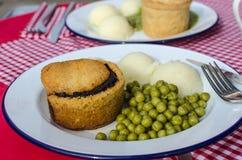 Английский традиционный пирог с картофельными пюре и горохами сада зелеными с подливкой на красной таблице Стоковая Фотография