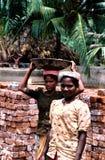 Андхра-Прадеш, Индия, около август 2002: Женские работники носят кирпичи стоковая фотография