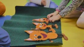Аниматоры играют с детьми в комнате детей в стикерах плюша игрушки с изображениями, только руками видимы, конец-вверх акции видеоматериалы