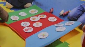 Аниматоры играют с детьми в комнате детей в стикерах плюша игрушки с изображениями, только руками видимы, конец-вверх видеоматериал