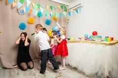 Аниматор играет с кричащими детьми на вечеринке по случаю дня рождения Стоковые Изображения RF