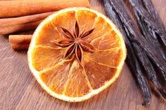 Анисовка звезды, душистая ваниль, циннамон и высушенный апельсин на деревянной поверхности Стоковая Фотография