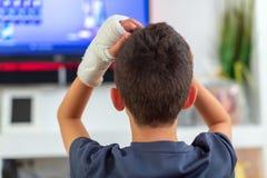 Анонимный мальчик со сломленной рукой смотря ТВ стоковое фото rf