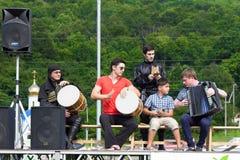 Ансамбль Adyghe музыкальный в черкесских национальных костюмах играя на этапе на предпосылке зеленого леса на этническом фестивал Стоковое Изображение RF