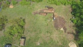 Антенна выкапывая ямы учреждения для нового дома мини затяжелителем и экскаватором акции видеоматериалы