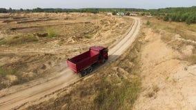 Антенна для красной большой тележки управляя в земном карьере с пылью летания за ей, концепцией индустрии Сцена Пустой грузовик видеоматериал