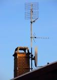 Антенна и спутниковая антенна-тарелка на печной трубе Стоковые Фото