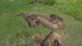 Антенна мини ямы учреждения затяжелителя и экскаватора выкапывая на травянистом поле сток-видео