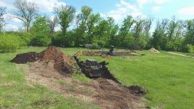 Антенна почвы раскопок бульдозера и экскаватора на травянистом поле согласно отмечать видеоматериал