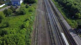 Антенна 4 строк длинного layng железных дорог вдоль зеленой линии кустов  акции видеоматериалы