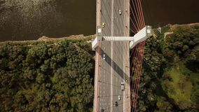 Антенна транспорта автомобилей на большом мосте при высокорослые штендеры пересекая большое реку видеоматериал