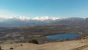 Антенна: трутень летая над озером долины леса, видом с воздуха снега покрыл горную цепь на Альпах, небо ясности голубое видеоматериал