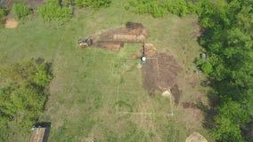Антенна экскаваторов выкапывая почву на зеленом поле с разметкой будущего дома акции видеоматериалы