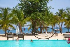 Антигуа, карибские острова Взгляд пляжа Galleon с ладонями, бассейном и кроватями пляжа Стоковые Фото
