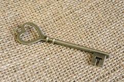 Антикварный бронзовый ключ на винтажной мешковине стоковые фото