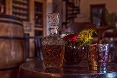 Античная бутылка вискиа na górze классической таблицы с свечами и розами стоковое изображение rf