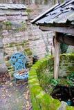 Античная водяная скважина с веревочкой и ведро в идилличной сцене Стоковая Фотография