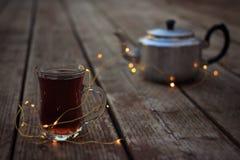 Античная кружка чайника и стекла горячего чая окруженная светами Стоковые Изображения