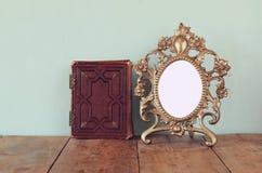 Античная пустая викторианская рамка стиля и старая книга на деревянном столе ретро фильтрованное изображение шаблон, подготавлива Стоковые Фотографии RF