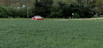Античное вождение автомобиля вниз с дороги окруженной деревьями и полем стоковые изображения rf