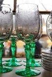Античные богато украшенные бокалы с зелеными стержнями и танцевать женщин выгравированные на их на полке перед окном стоковые изображения rf
