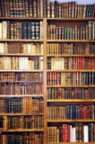 Античные книги на полке библиотеки Стоковое Фото