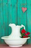 Античные кувшин и таз воды с красными цветками выдержанной предпосылкой древесной зелени Стоковые Фото