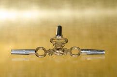 Античные латунные ключи карманного вахты кладя на золотую поверхность Стоковые Фото