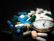 Античные часы на пестротканом лекарства и капсулы на черной предпосылке конец вверх Мы против лекарств лекарств анти-, лечения вн Стоковое фото RF