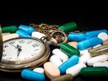 Античные часы на пестротканом лекарства и капсулы на черной предпосылке конец вверх Мы против лекарств лекарств анти-, лечения вн Стоковые Изображения RF