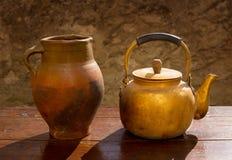 Античный латунный чайник на ретро деревянной таблице и глина раздражают Стоковая Фотография RF