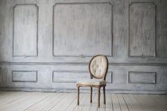 Античный белый стул над роскошными светлыми элементами roccoco прессформ штукатурки барельеф дизайна стены Стоковое фото RF