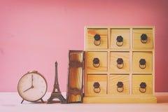 античный комод с ящиками рядом с старой книгой и Эйфелевой башней Стоковое Изображение