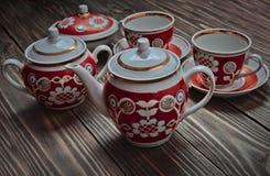 Античный комплект керамических чайников, чашек, поддонников на деревянном столе Стоковое Изображение RF