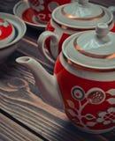Античный комплект керамических чайников, чашек, поддонников на деревянном столе Стоковое Фото