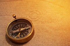Античный латунный компас в песке с следом ноги Стоковое фото RF