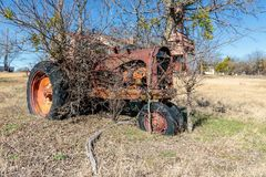 Античный трактор сидит на старой мельнице Кроуфорда в Walburg Техасе Стоковое Фото
