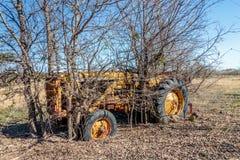 Античный трактор сидит на старой мельнице Кроуфорда в Walburg Техасе Стоковые Фото