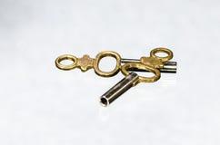2 античных латунных ключа карманных вахты кладя на белую поверхность Стоковое Фото