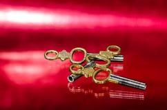 3 античных латунных ключа карманных вахты кладя на красную поверхность Стоковые Фото