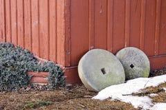 2 античных жернова полагаясь против деревенского красного деревянного строения Стоковая Фотография