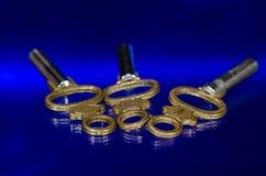 3 античных латунных ключа карманных вахты кладя на голубую поверхность Стоковые Фото